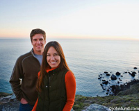 Picture of a Hispanic couple in front of a body of water, probably the ocean.  The woman is in front with her boyfriend behind her. They are both smiling at the camera and dressed in warm clothing.
